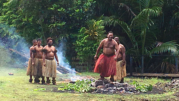 A Fijian firewalker walking on hot stones